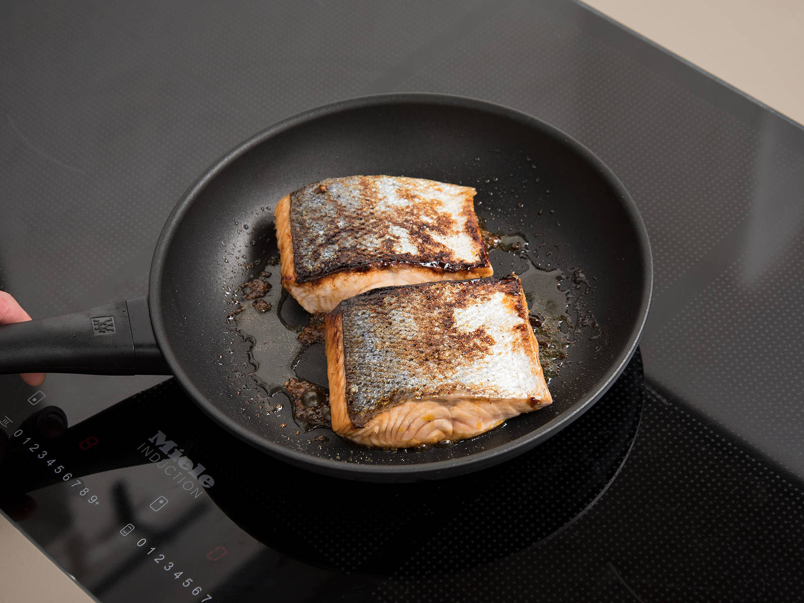 Heat the rest of the olive oil in a frying pan over medium-high heat, and fry the salmon skin side down for approx. 2 min. Flip the fillets over and brush with remaining syrup. Cook for another 3 - 4 min. or until cooked to desired level of doneness.