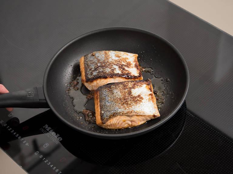 开中高火,在一个煎锅中加热橄榄油,然后将三文鱼带皮一面朝下,煎2分钟。翻面后,再刷一层糖浆,煎3-4分钟,或者直至煎出理想的熟度。