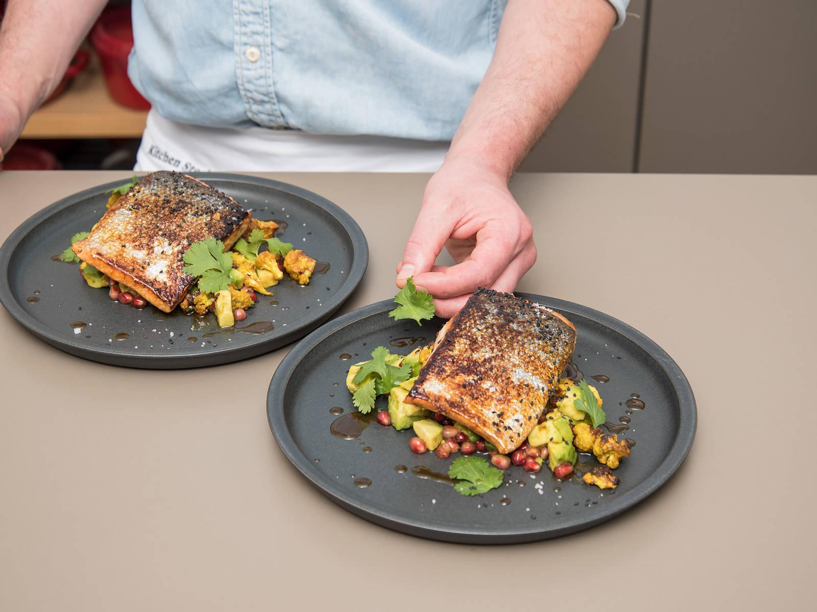 Lachs mit Avocado-Blumenkohlsalat servieren und mit schwarzen Sesamkörnern und Koriander garnieren. Guten Appetit!