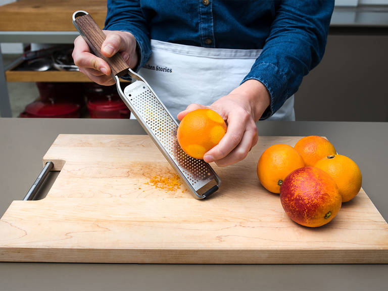 Pre-heat oven to 175°C/350°F. Rinse the blood oranges thoroughly with hot water and, using a fine grater, grate the zest of 1/5 of the oranges. Reserve zest. Cut off the top and bottom of the blood oranges and carefully removing the peel if you'd like. Slice the oranges thinly, removing any of the pithy core.