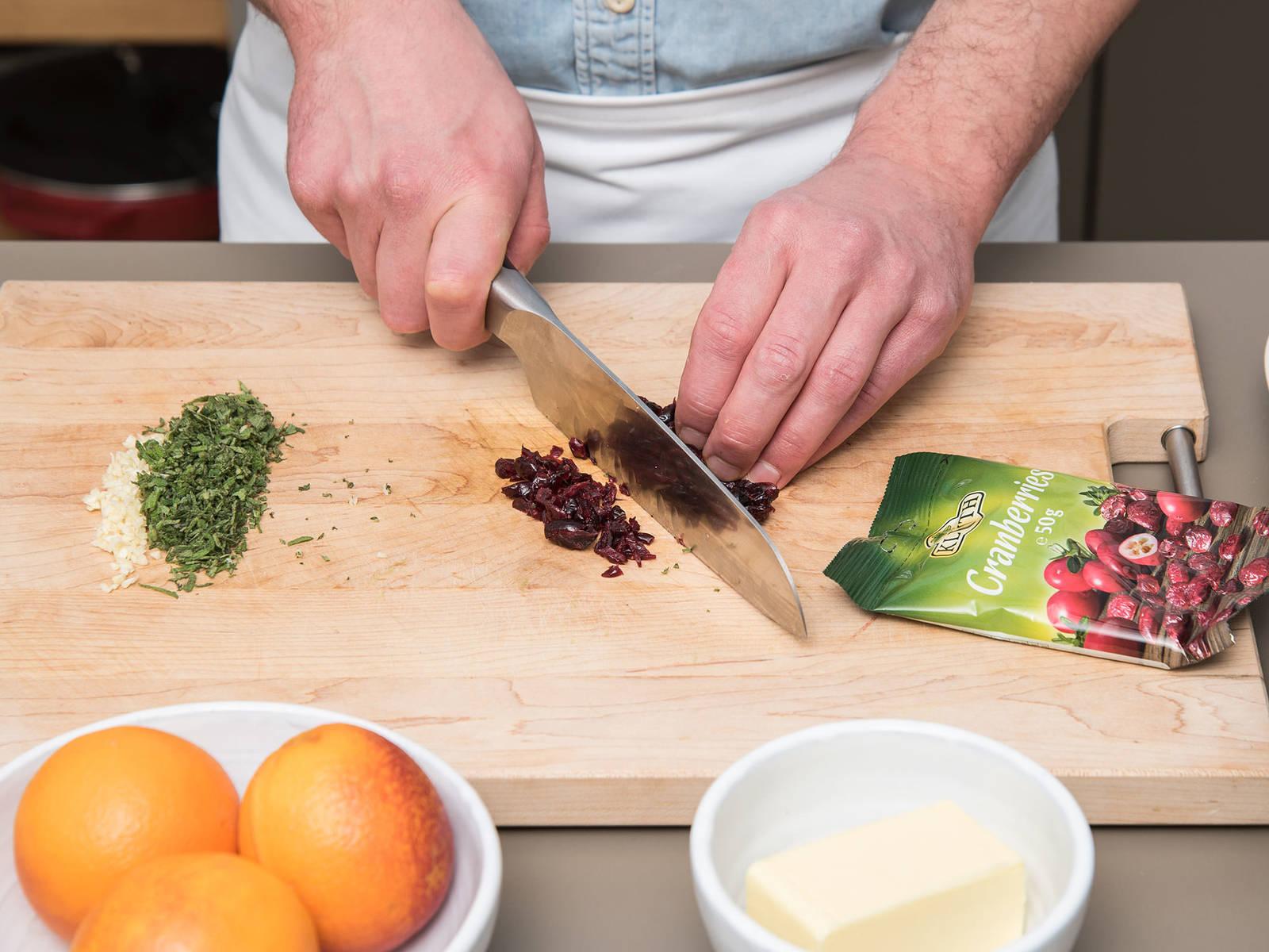 Knoblauch, etwas mehr als die Hälfte der Salbeiblätter und Cranberrys hacken. Mit einer feinen Reibe eine Blutorange abreiben und anschließend den Saft auspressen. Abrieb und Saft beiseitestellen. Die restlichen Blutorangen in Scheiben schneiden.