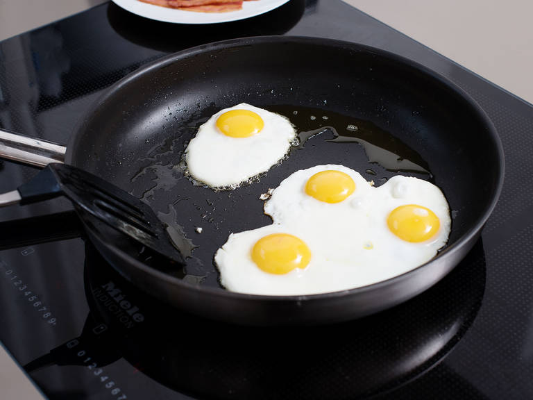 Heat some oil in a second frying pan and fry eggs for approx. 3 – 4 min. The egg yolk should be a bit runny and the edges, crisp. Season to taste with salt and pepper. Remove from pan and set aside.