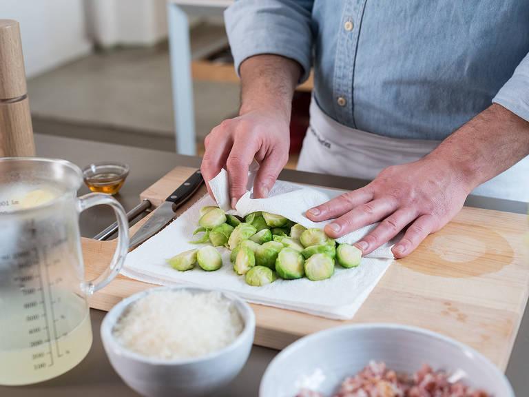 Rosenkohl abgießen und mit Küchenpapier trocken tupfen. Etwas Kochwasser abschöpfen und beiseitestellen.