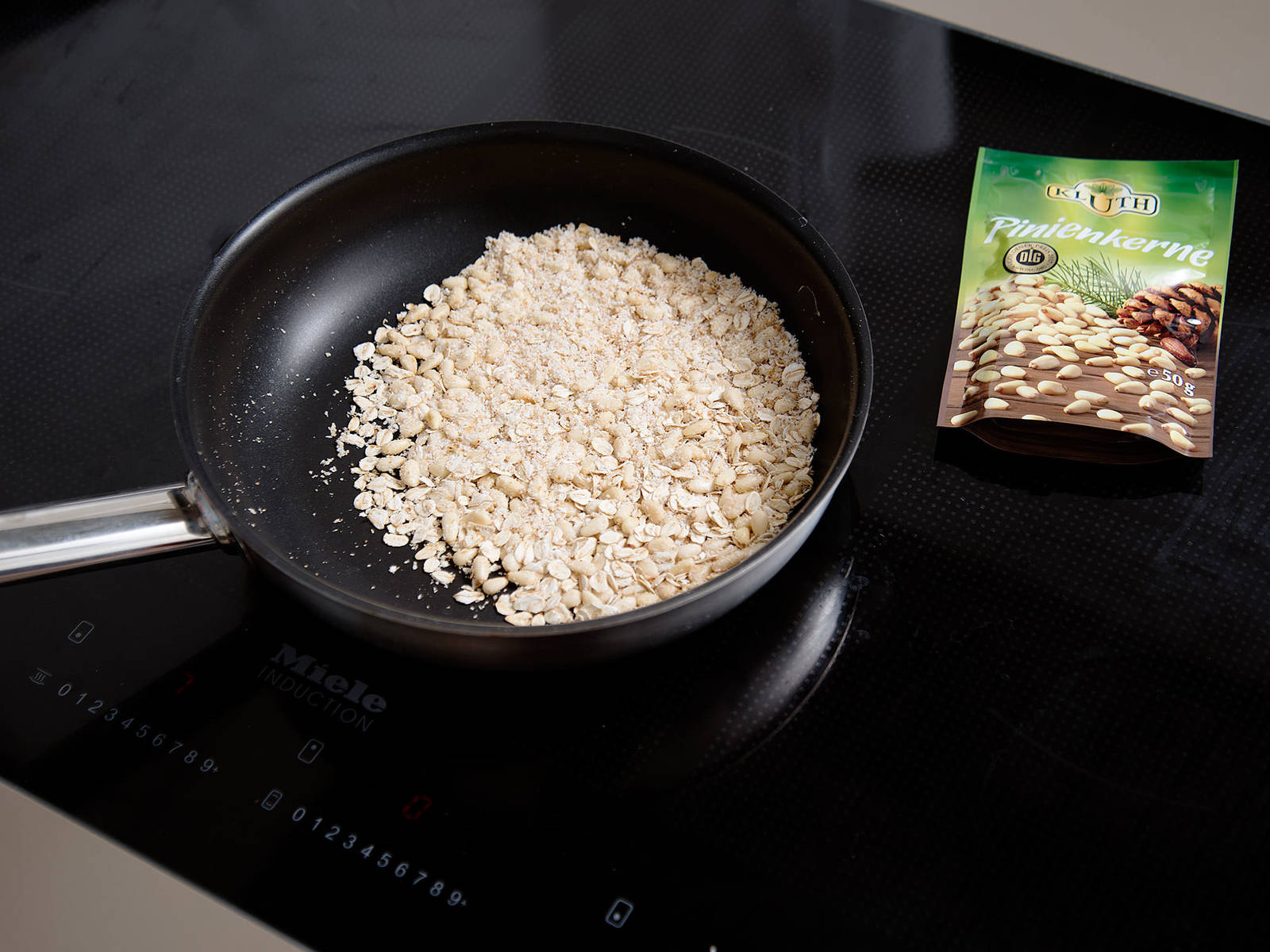 Pinienkerne, Haferflocken und Kokosraspeln in einer Pfanne goldbraun rösten. Butter und Ahornsirup dazugeben, vermengen und köcheln lassen. Pfanne vom Herd nehmen und abkühlen lassen.