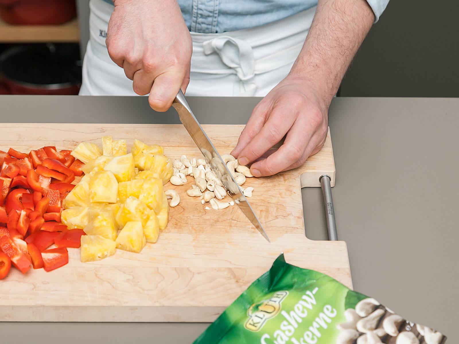 菠萝削皮后切片,灯笼椒也切片,待用。洋葱去皮切丁。大略剁碎腰果。