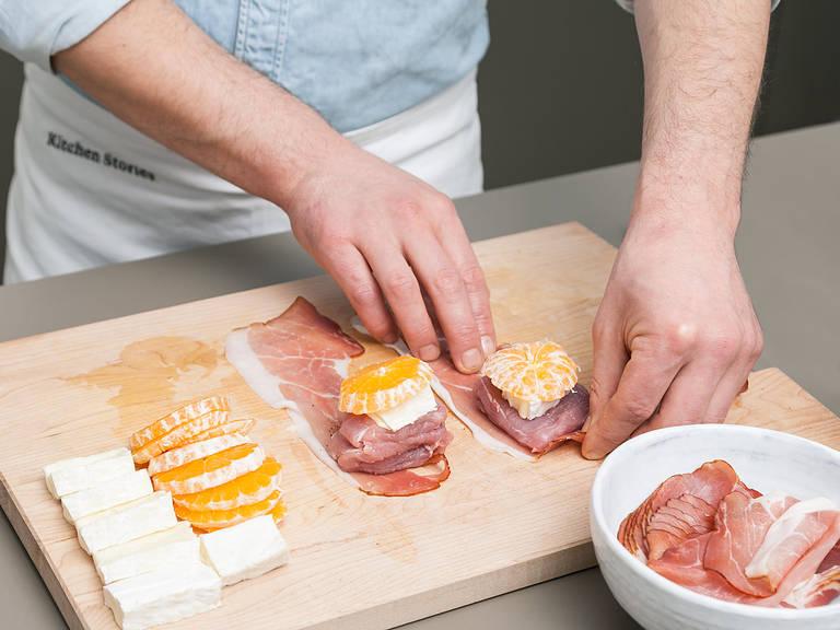 烤箱预热至200°C。将一部分红橘剥皮。红橘与芝士切厚片。猪肉切成厚约3厘米的片状。将猪肉片放在黑森林火腿片上,撒上盐与胡椒调味。在猪肉片上放上一片芝士与一片红橘,并裹好。放到烤盘中。