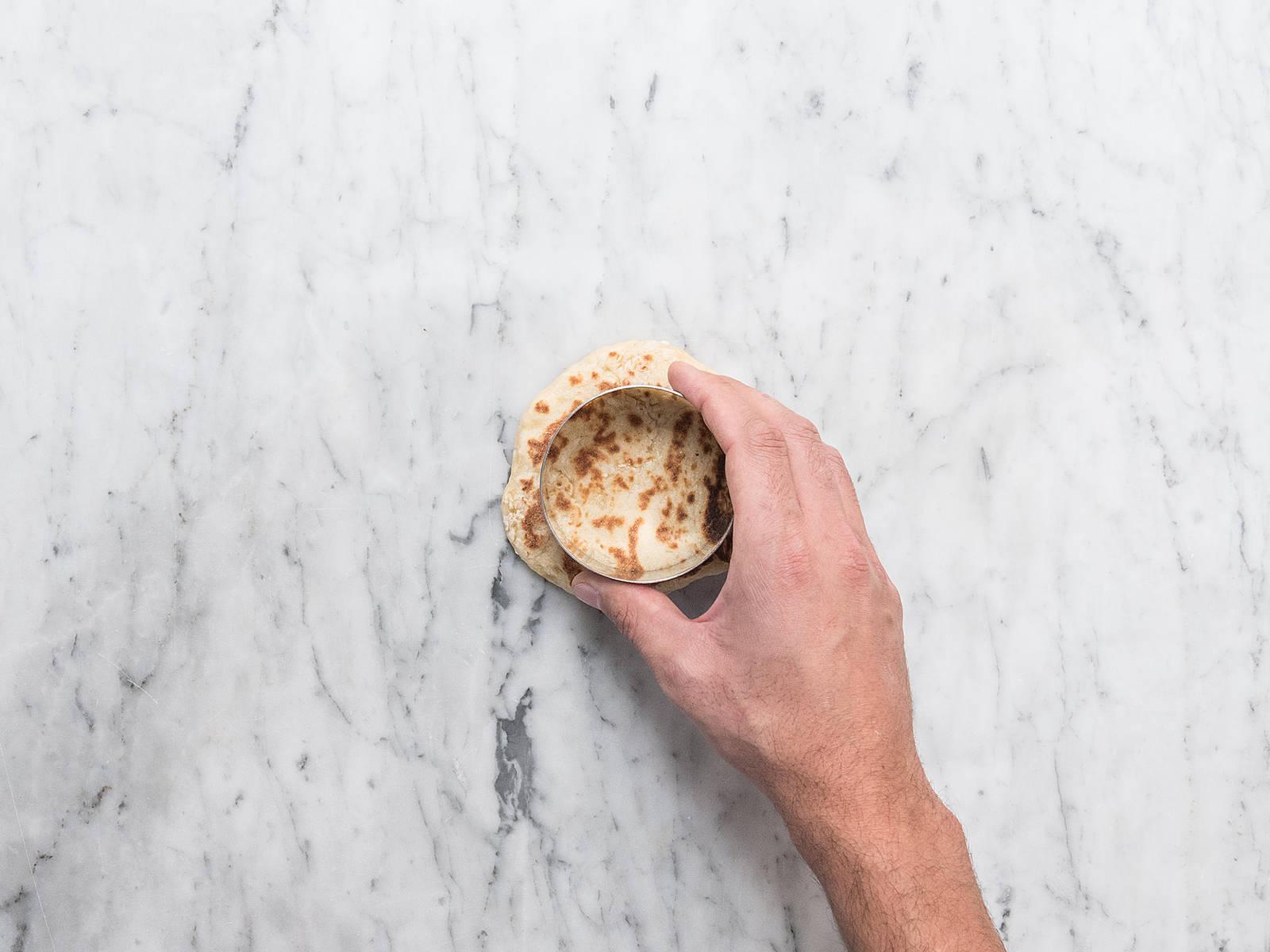 Das Naan Brot mit einer runden Ausstechform oder einem Glas in 6 gleich große Kreise ausstechen. Einen Kreis mit Nutella bestreichen, einen weiteren Kreis darauflegen, wieder mit Nutella bestreichen und mit einem dritten Kreis bedecken. Das Ganze mit den verbleibenden 3 Stücken wiederholen.