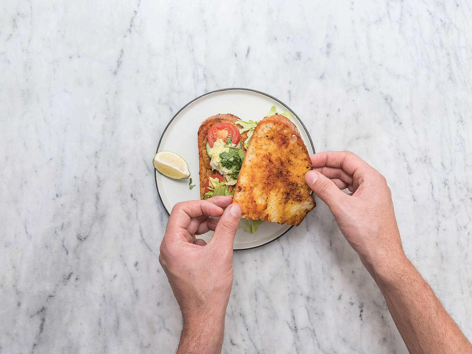 Transfer bread slices to a serving plate and assemble sandwich with lettuce, tomato, cucumber, fresh herbs, a squeeze of lime, and top with chicken tikka. Enjoy!
