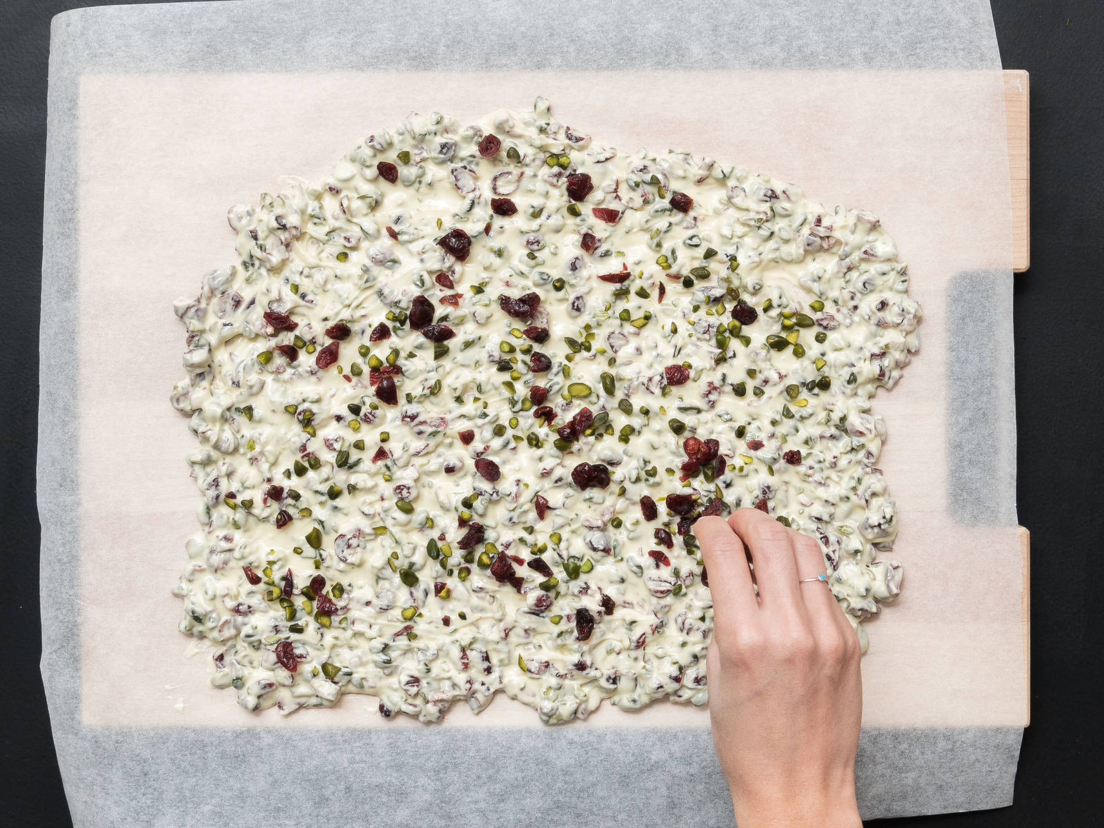 Spread the chocolate mixture over parchment paper, approx. 0.5-cm/0.25-in. thick, and sprinkle remaining pistachios and cranberries on top.