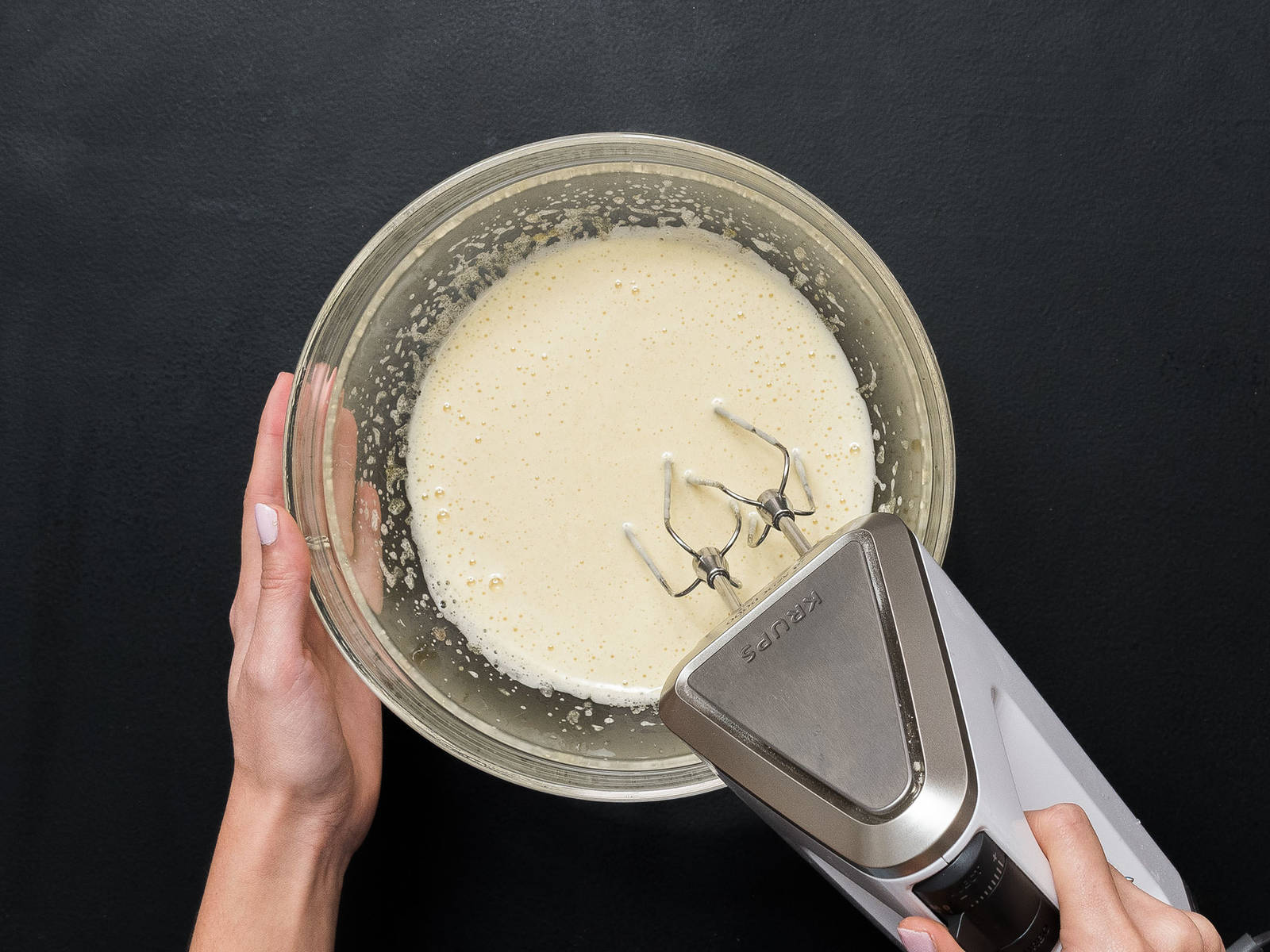 Eier, Zucker und Vanillezucker mit einem Handrührgerät in einer großen Schüssel verrühren.