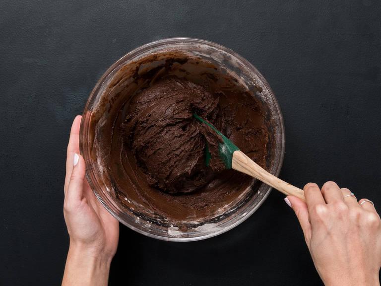 Schokoladen-Butter-Mischung zugeben und gut umrühren. Die trockenen Zutaten nach und nach zugeben und alles zu einem festen Teig formen.