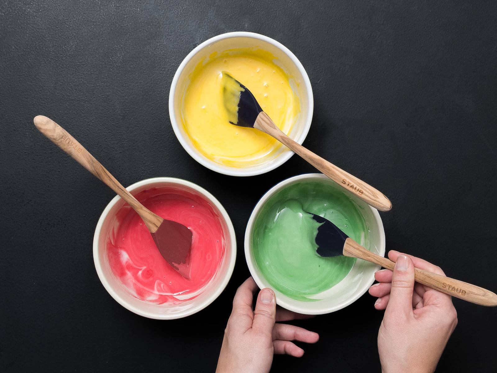 In der Zwischenzeit Puderzucker, Wasser und Zitronensaft zu einer dickflüssigen Glasur verrühren. Sie sollte sehr langsam vom Löffel laufen. Wenn die Glasur zu dick ist, etwas Wasser dazugeben bis die gewünschte Konsistenz erreicht ist. Glasur auf drei Schüsseln aufteilen und den Inhalt jeder Schüssel mit einer anderen Lebensmittelfarbe einfärben. Jede Glasur in einen eigenen Spritzbeutel mit Tülle füllen.