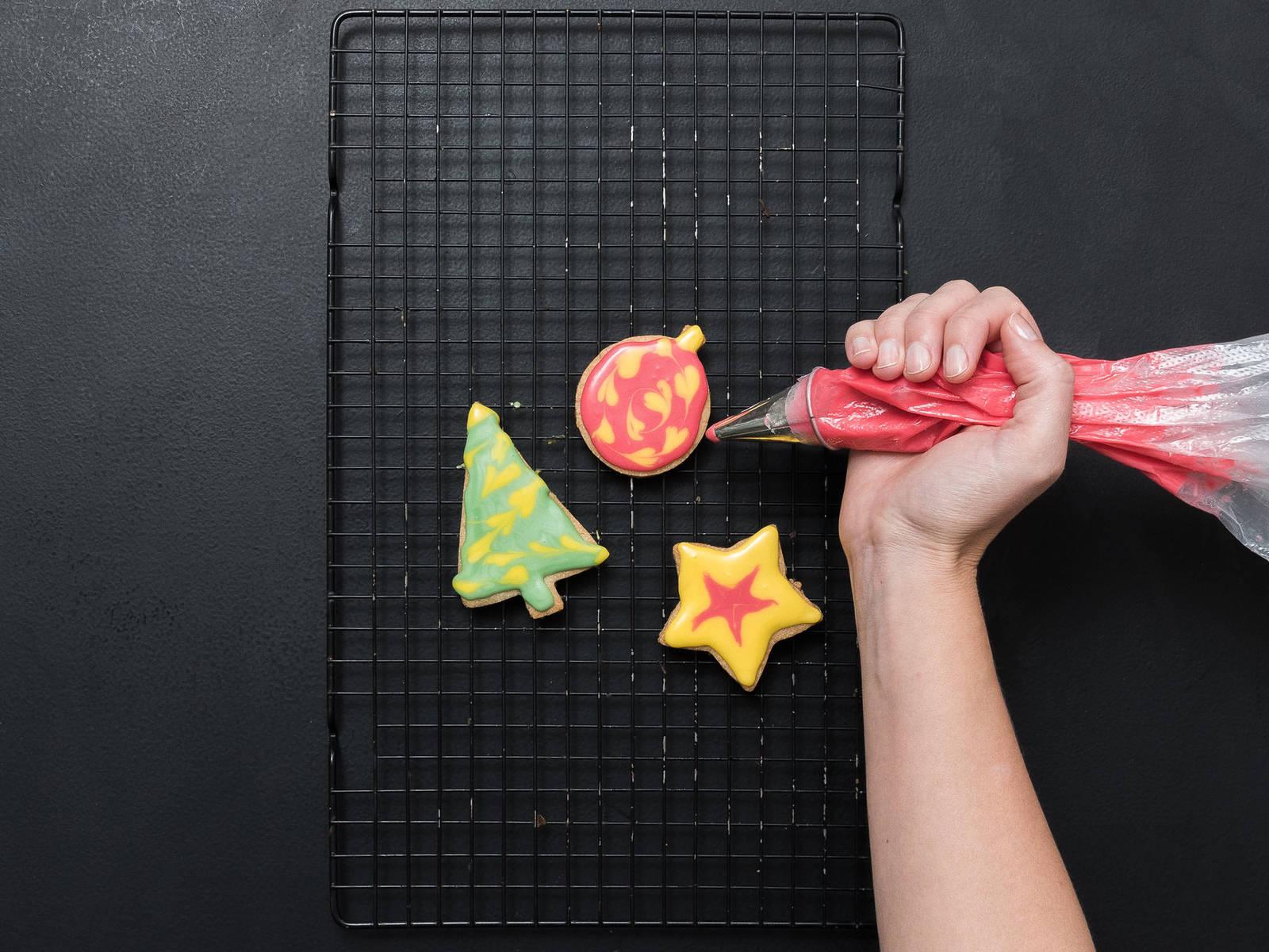 Die Plätzchen mit der Glasur verzieren. Um ein Muster zu erzeugen, zunächst eine Grundschicht Glasur auftragen. Anschließend mit einer Glasur in einer anderen Farbe Linien oder Punkte darauf setzen und mit einem Zahnstocher die obere Glasur durch die untere Schicht ziehen. Über Nacht trocknen lassen. Guten Appetit!