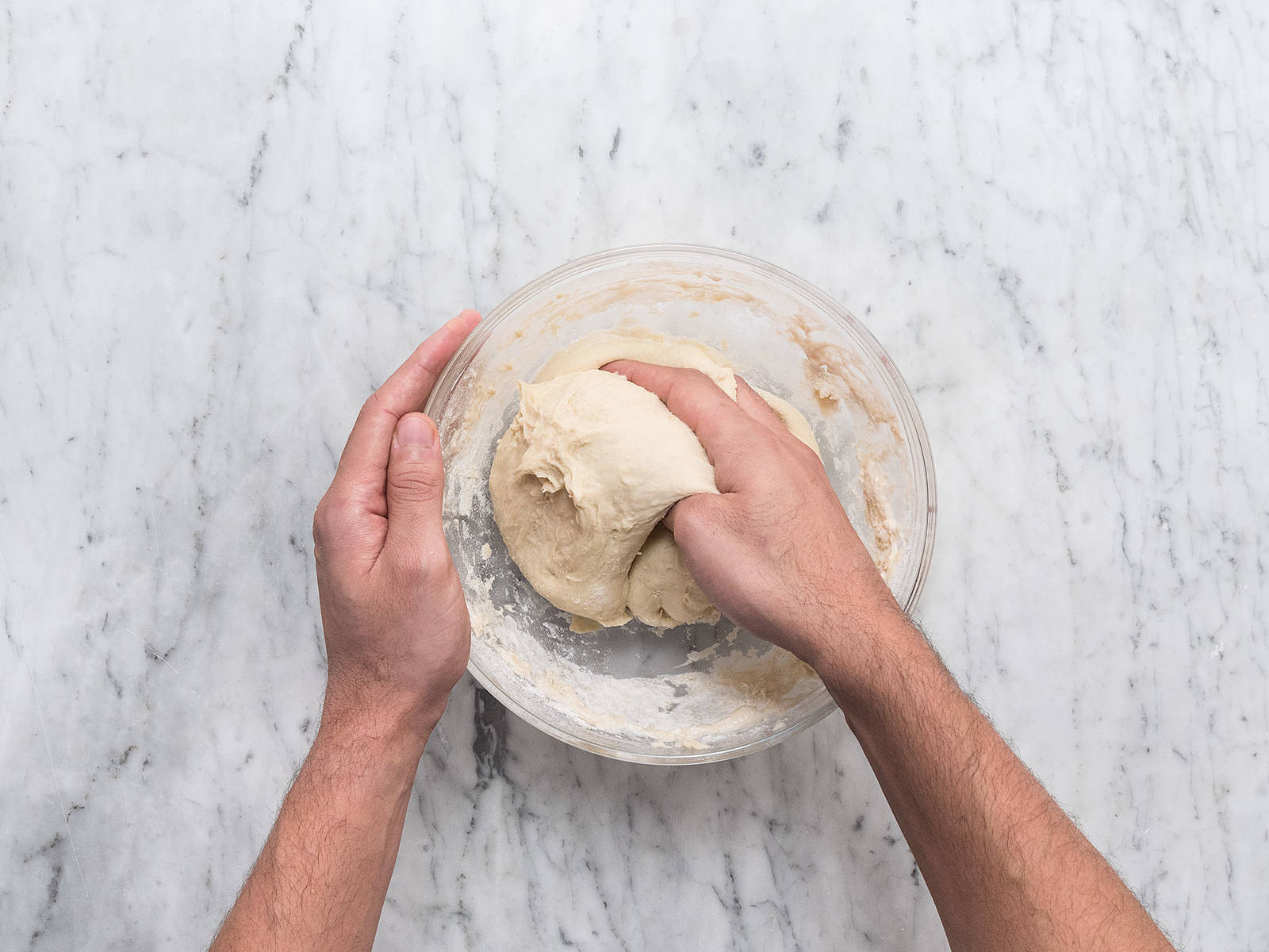 在混合物中加入面粉,和面,将面团揉至顺滑。盖住碗,静置一旁发酵约1小时。