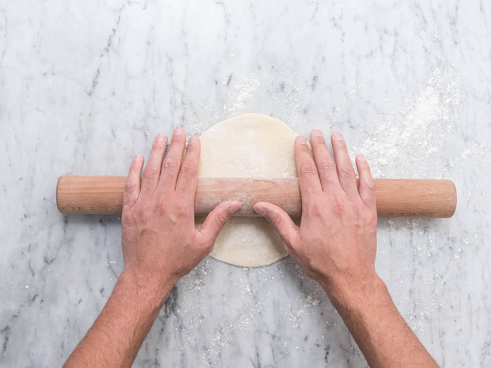在工作台上撒上面粉,将面团分成大小相同的圆饼。用擀面杖将每一个小面团擀成0.5厘米厚的圆形面皮。