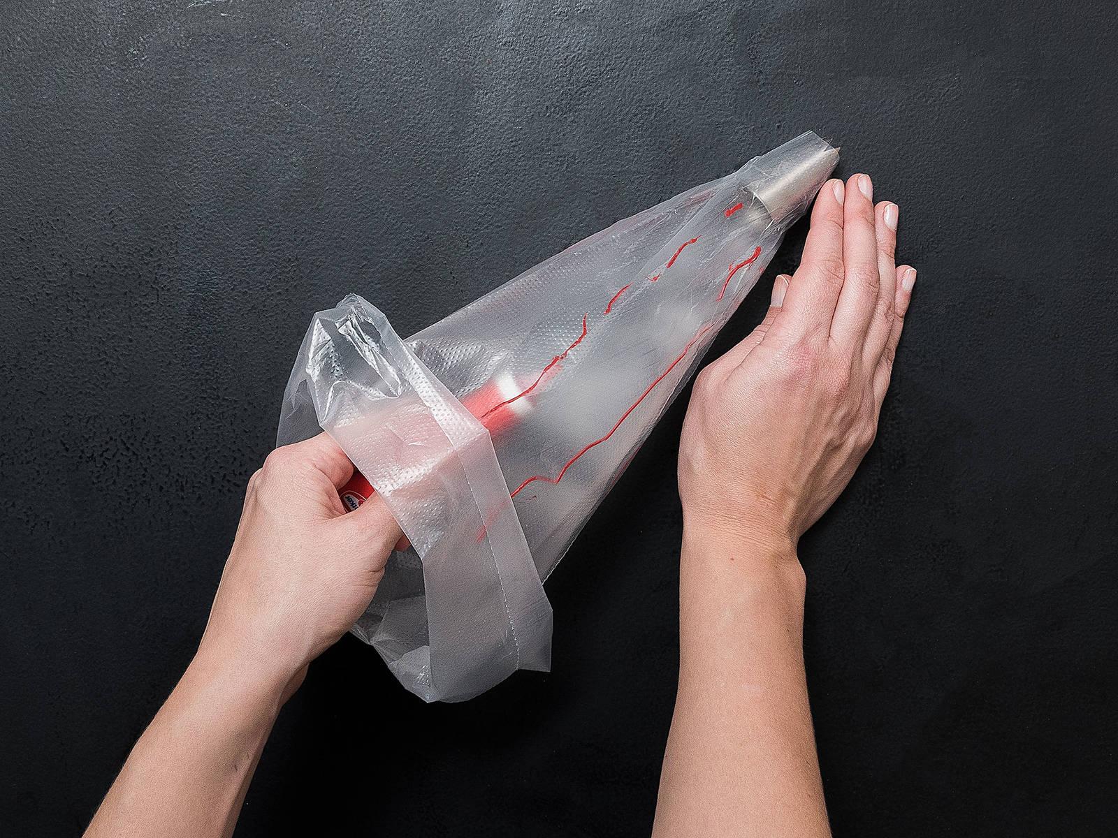 Backofen auf 175°C vorheizen. Tülle in die Spritztüte setzen und mit roter Lebensmittelfarbe 4 Streifen entlang der Seiten der Spritztüte ziehen.