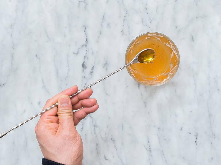 Zitronengras-Rum, naturtrüben Apfelsaft, gemahlenen Zimt und Honig in ein Cocktailglas geben und gut verrühren.