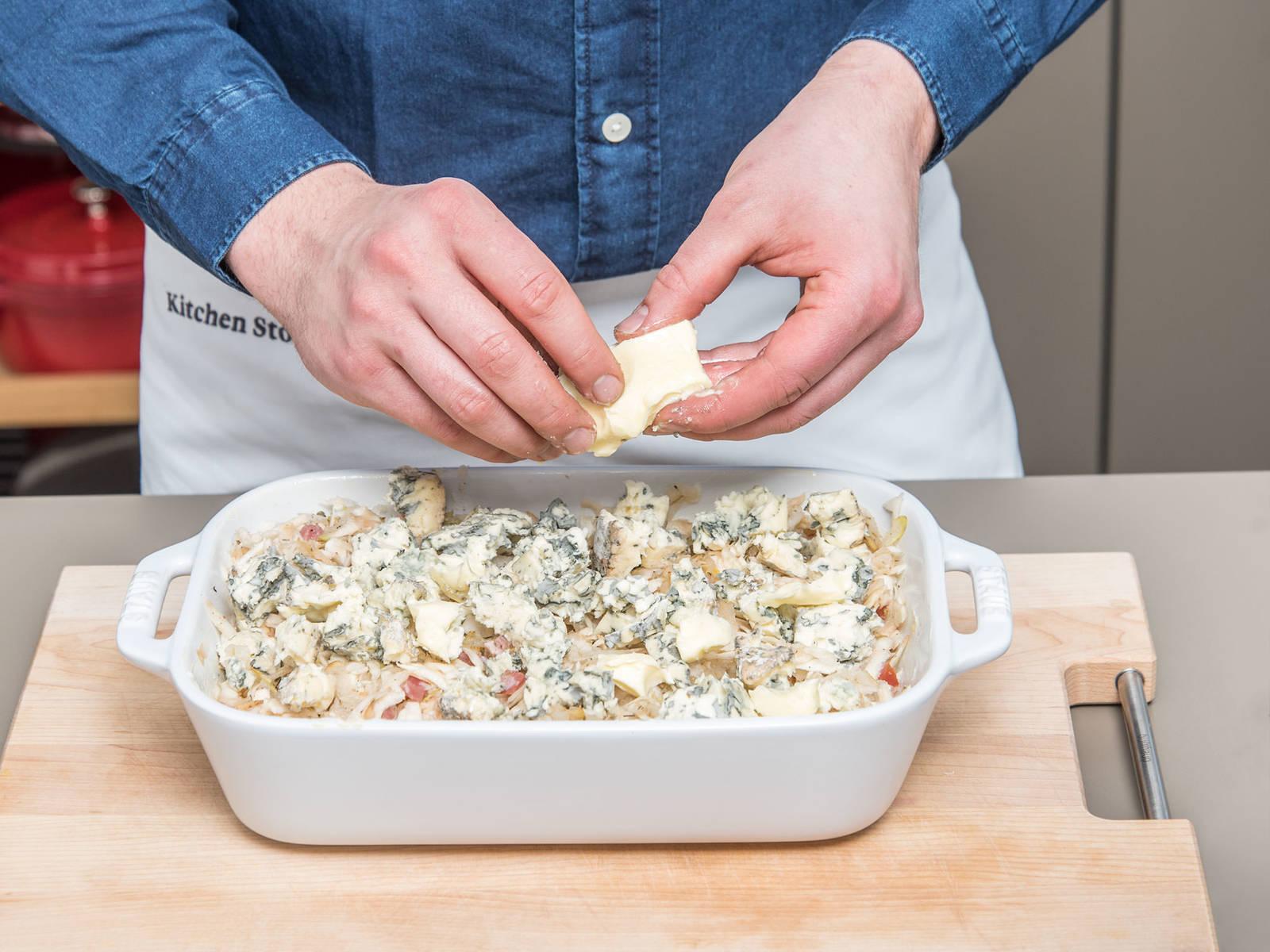 将上一步做好的芹菜根、梨、培根混合物倒入烤盘中。倒上蔬菜高汤。捏碎蓝芝士,和黄油、杏仁粉一起均匀撒到芹菜根和梨上。