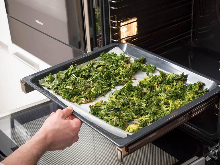 将羽衣甘蓝均匀地在铺有烘焙纸的烤盘上铺一层。以100℃烤30分钟,或直至羽衣甘蓝变得焦脆且稍微呈棕色。从烤箱中取出,彻底放凉后享用!
