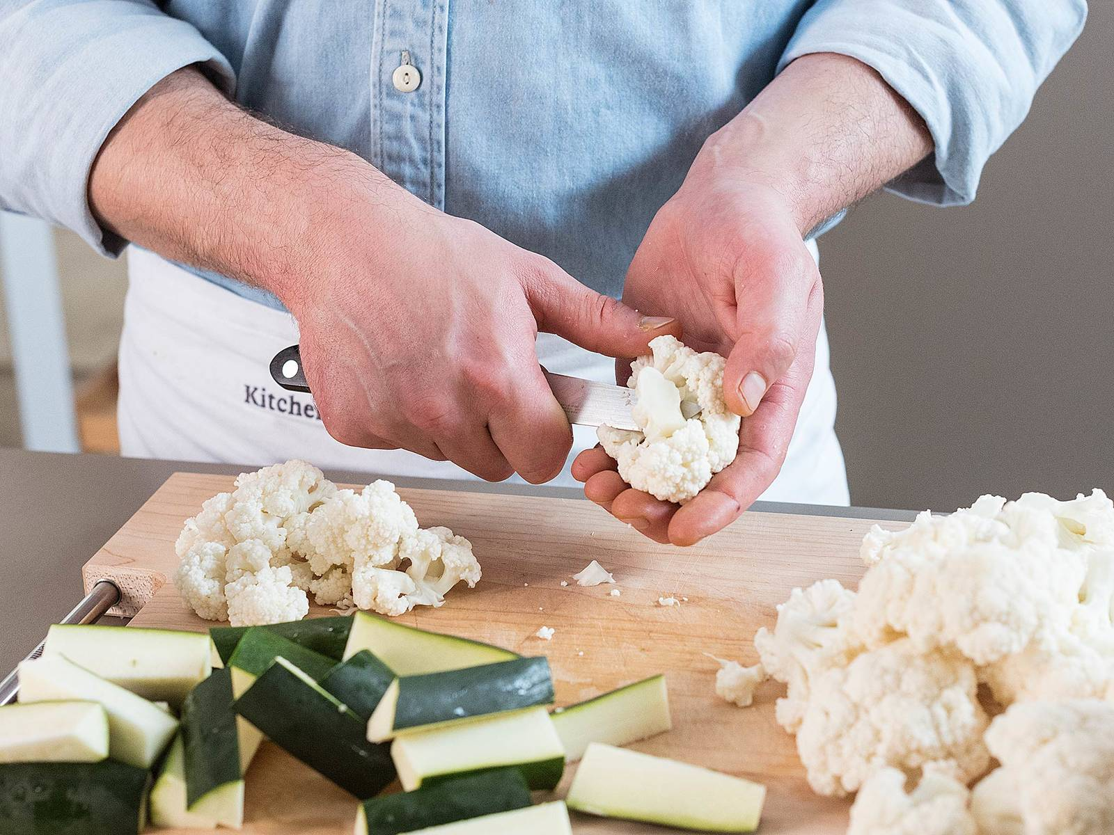Währenddessen Zucchini in mundgerechte Stücke schneiden, anschließend für ca. 15 Min. mit Öl in einer Grillpfanne anbraten. Blumenkohl vom Strunk befreien und ebenfalls in mundgerechte Stücke schneiden. In einer Pfanne bei mittlerer bis hoher Hitze ca. 15 Min. braten. Zucchini und Blumenkohl mit Salz und Pfeffer abschmecken und beiseitestellen.