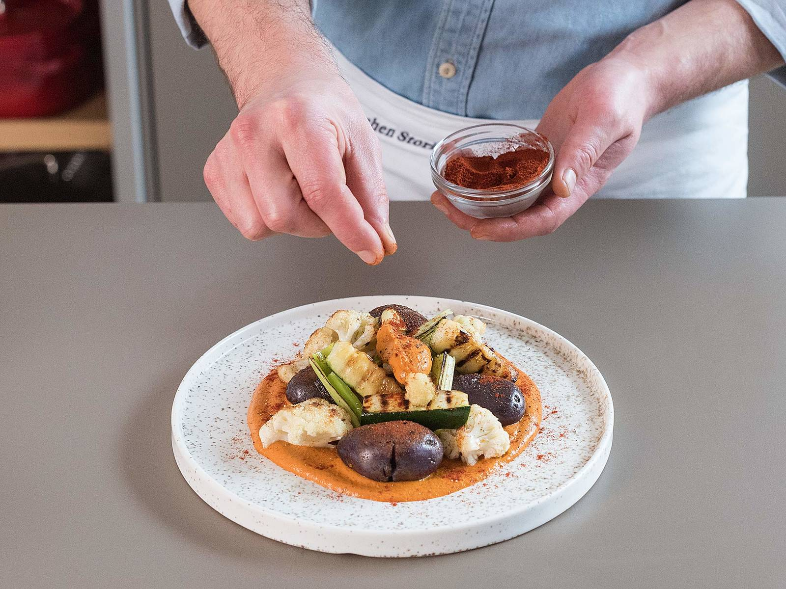 Mound the romesco sauce in the center of a large plate and serve with crushed potatoes, seared leeks, zucchini, and cauliflower. Garnish with a drizzle of olive oil and a sprinkle of salt. Enjoy!
