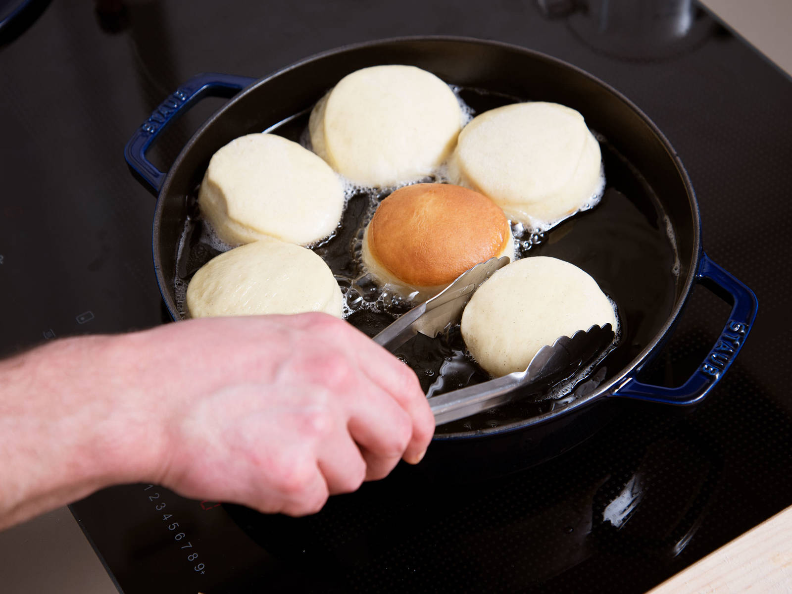 Add oil to a pot and heat until it reaches 170°C/340°F. Carefully add dough circles one by one, then close lid and let fry for approx. 2 – 3 min. Flip carefully and let fry on the other side for approx 2 – 3 min. more. Remove doughnuts from pot and drain on a paper towel-lined plate.