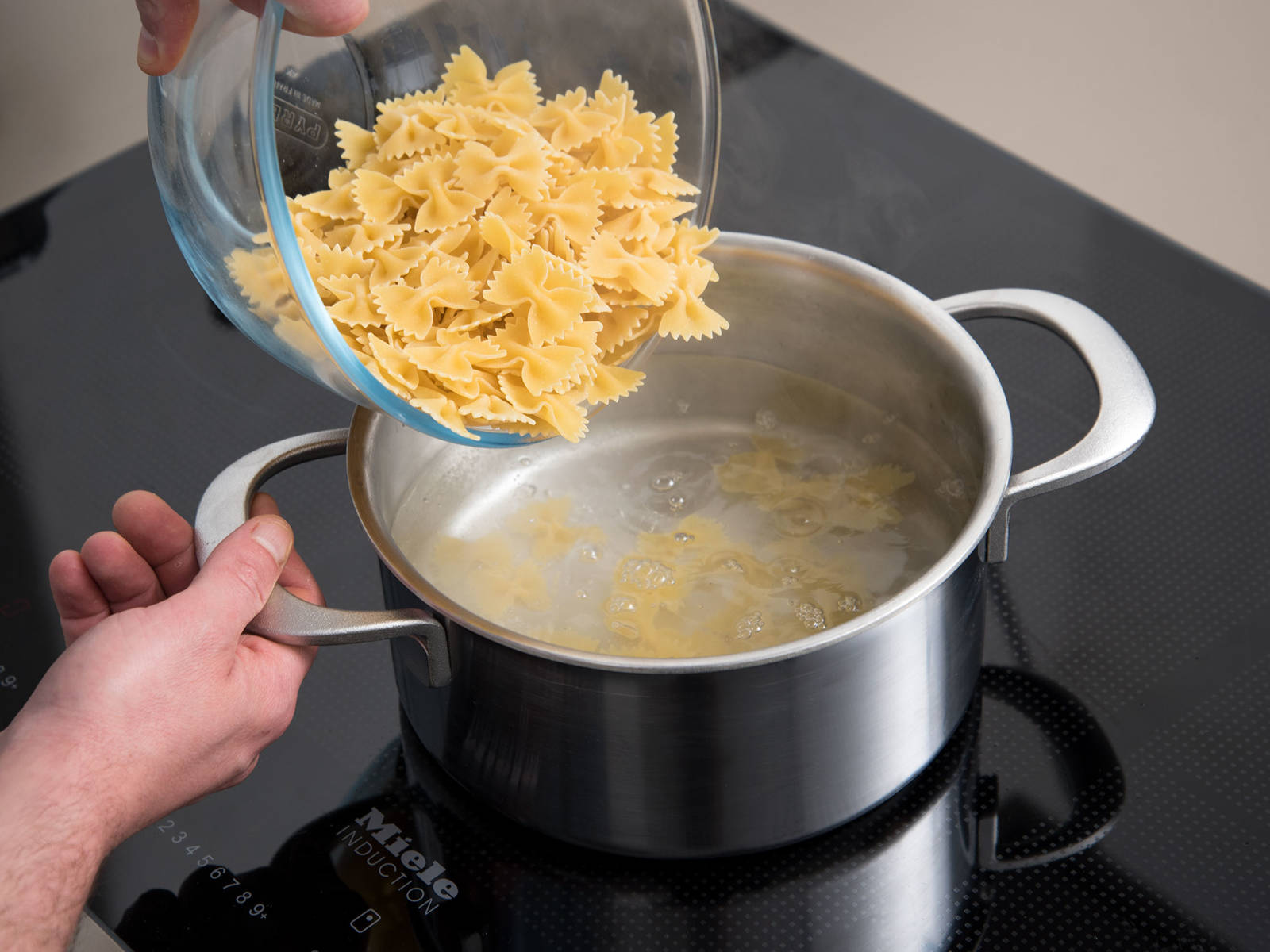 In another pot of boiling, salted water, cook the farfalle until al dente and strain into colander and drain.