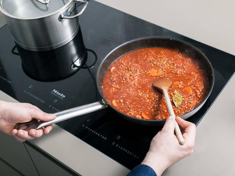 Eine Pfanne über mittlerer Hitze erwärmen und Butterschmalz darin schmelzen. Zwiebeln und Knoblauch darin für ca. 1 Min. anbraten. Karotte dazugeben und für ca. 2 Min. anbraten. Tomatenmark dazugeben und nochmal kurz braten. Mit Rotwein ablöschen. Gemüsebrühe, Lorbeerblätter, rote Linsen und gewürfelte Tomaten in die Pfanne geben. Gut vermengen und abgedeckt für ca. 20 Min. köcheln lassen.
