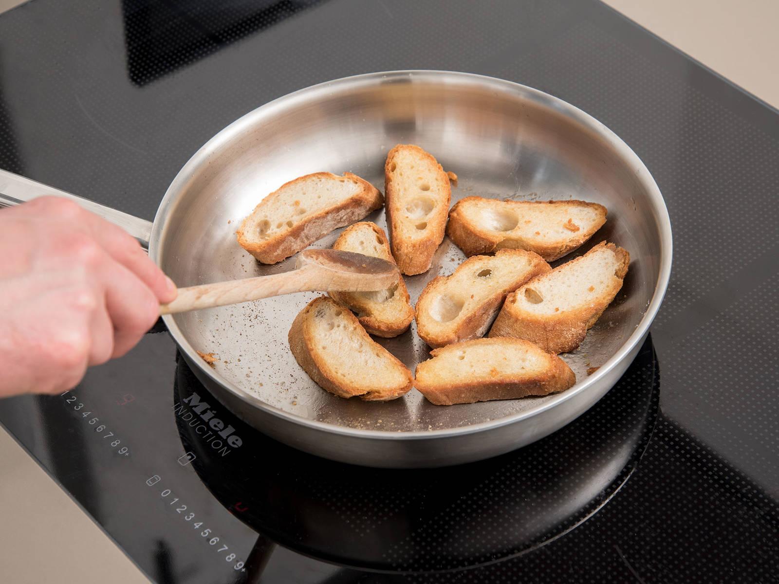Baguette in Scheiben schneiden. Butter in einer Pfanne schmelzen und die Baguettescheiben von beiden Seiten knusprig anrösten. Mit Salz würzen.
