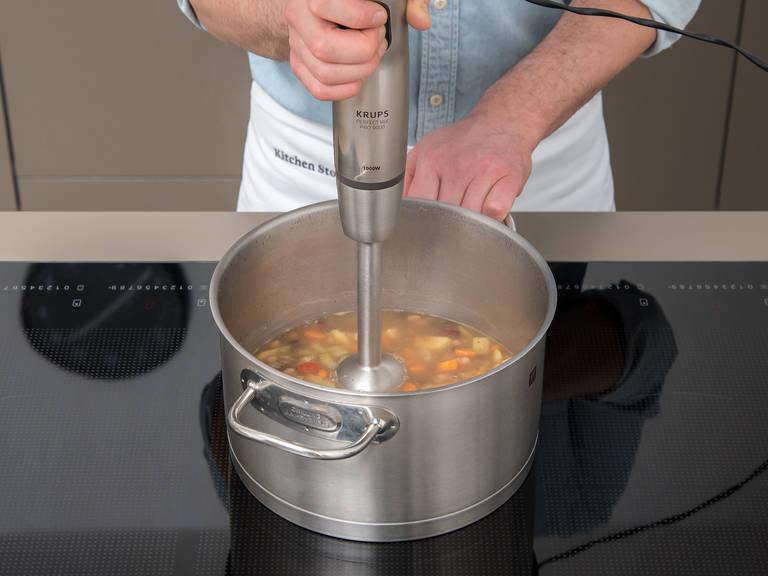 将皱叶甘蓝切成细条。汤煮好后,将其搅打成柔滑泥状。如有需要,可加水调节稠度。倒入剩余的豆子和皱叶甘蓝,再煮5-10分钟。