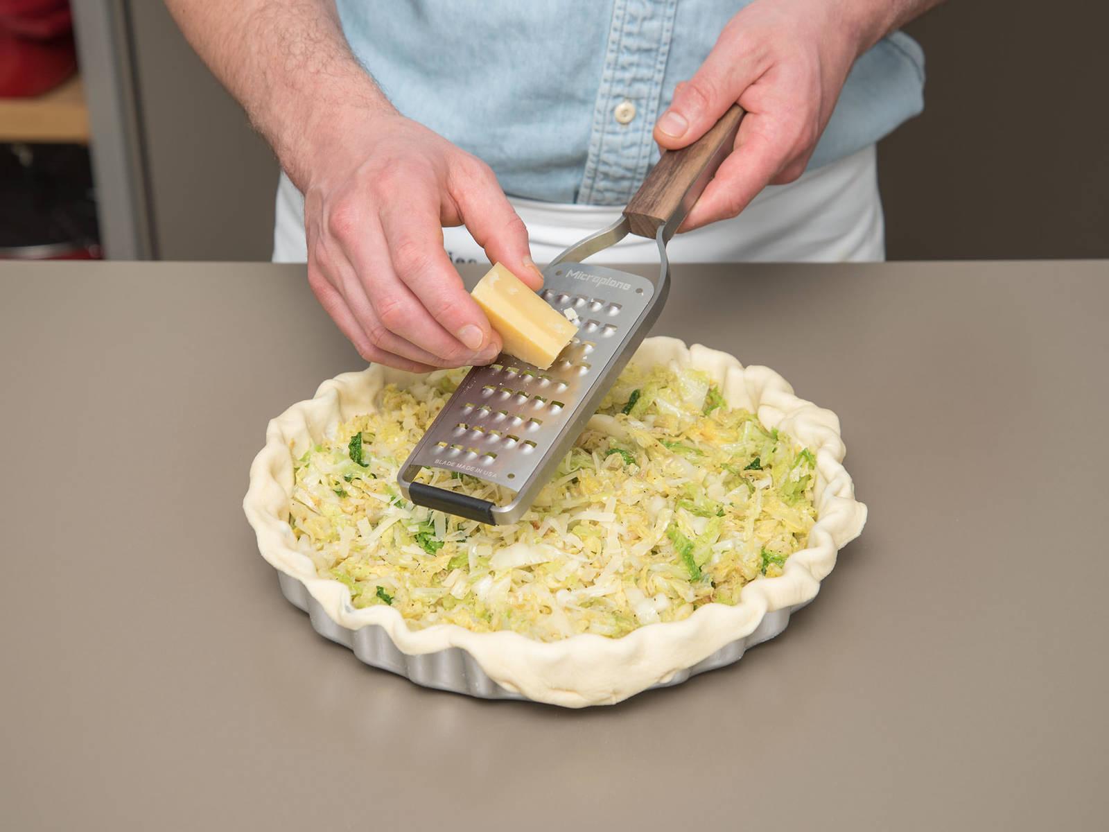 将三分之二的阿尔卑斯干酪切成薄片,铺在烤盘底部。在面团中间放上一小堆甘蓝。将剩余的干酪擦屑,撒在甘蓝上。