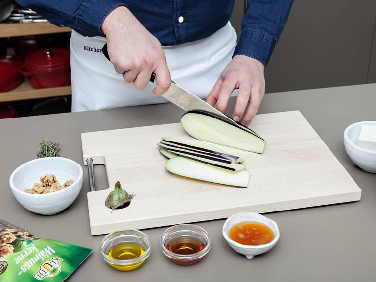 Backofen auf 220°C vorheizen. Strunk der Aubergine abschneiden und in dünne Scheiben schneiden. Auberginenscheiben auf einem Backblech verteilen, mit Olivenöl bestreichen und salzen. Ca. 20 Min. backen und nach der Hälfte der Backzeit wenden.
