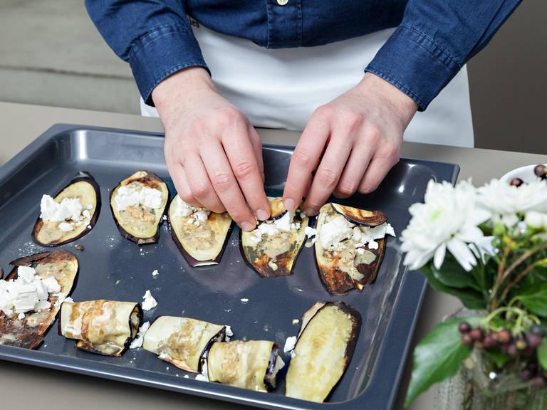 Gebackene Auberginenscheiben mit der Walnuss-Thymian-Paste bestreichen und Ziegenkäse auf den Auberginenscheiben verteilen. Die Scheiben vorsichtig einrollen.