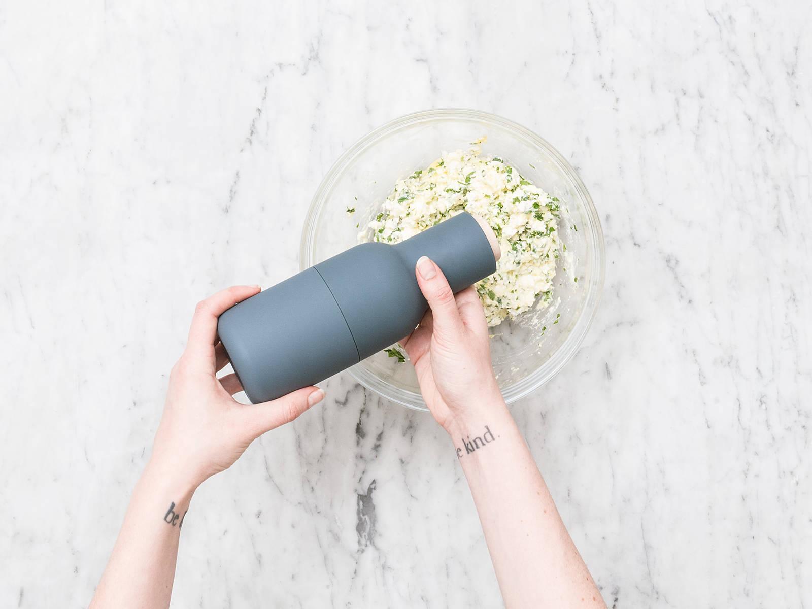 剁碎欧芹,置于一旁。用手将绵羊芝士捏碎,放入碗中。加入欧芹和鸡蛋。撒盐与胡椒调味,搅拌混合。