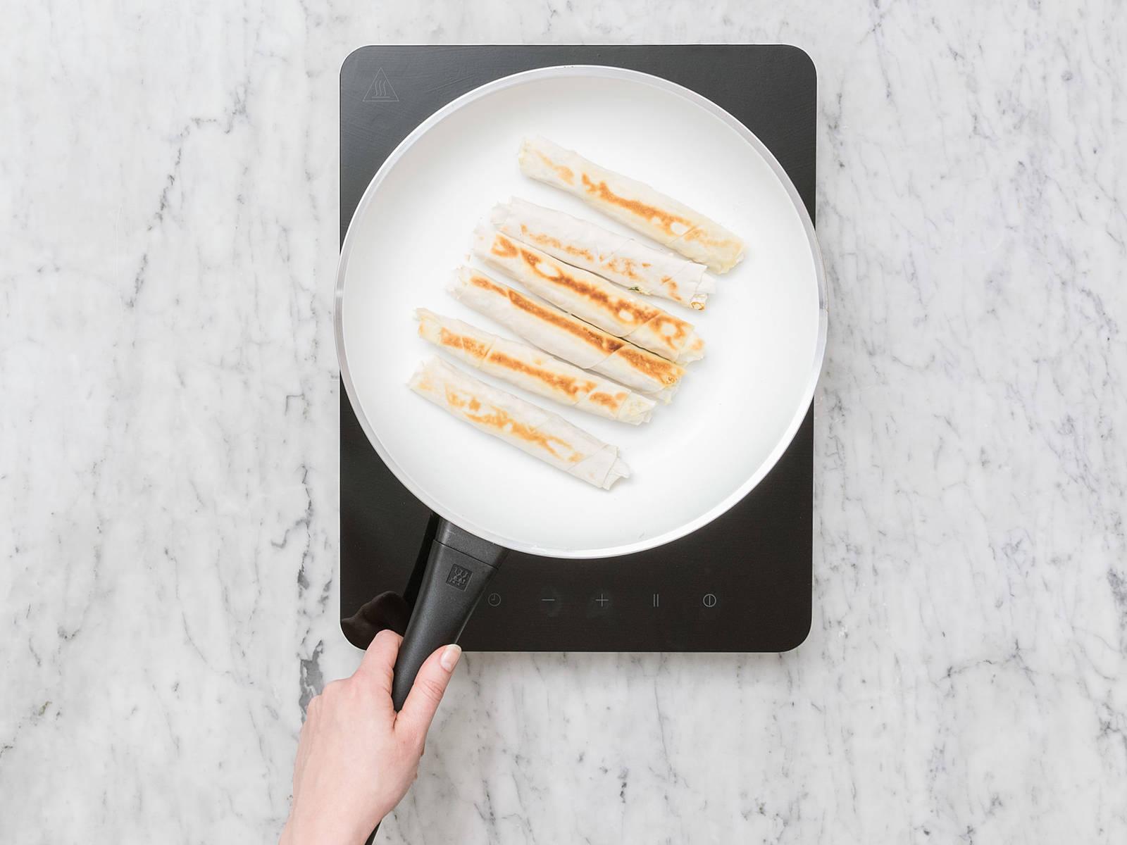 在煎锅中加热植物油,煎芝士卷各面4-5分钟,直至面饼变得焦脆且呈金棕色。放到厨房纸上,吸干多余油分,然后趁热或放凉后享用。祝好胃口!