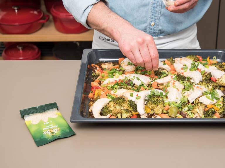 将烤盘从烤箱中取出。将剩余酱汁淋在鸡胸肉上,并将鸡肉放在蔬菜上。以200°C再烤约10分钟,直至鸡肉烤熟。撒上切好的葱圈,剩余的芝麻以及香菜。尽情享用吧!