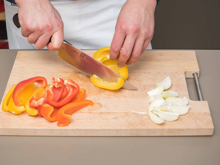 Pre-heat oven to 220°C/425°F on convection. Peel and chop onions. Cut bell peppers into wide strips.