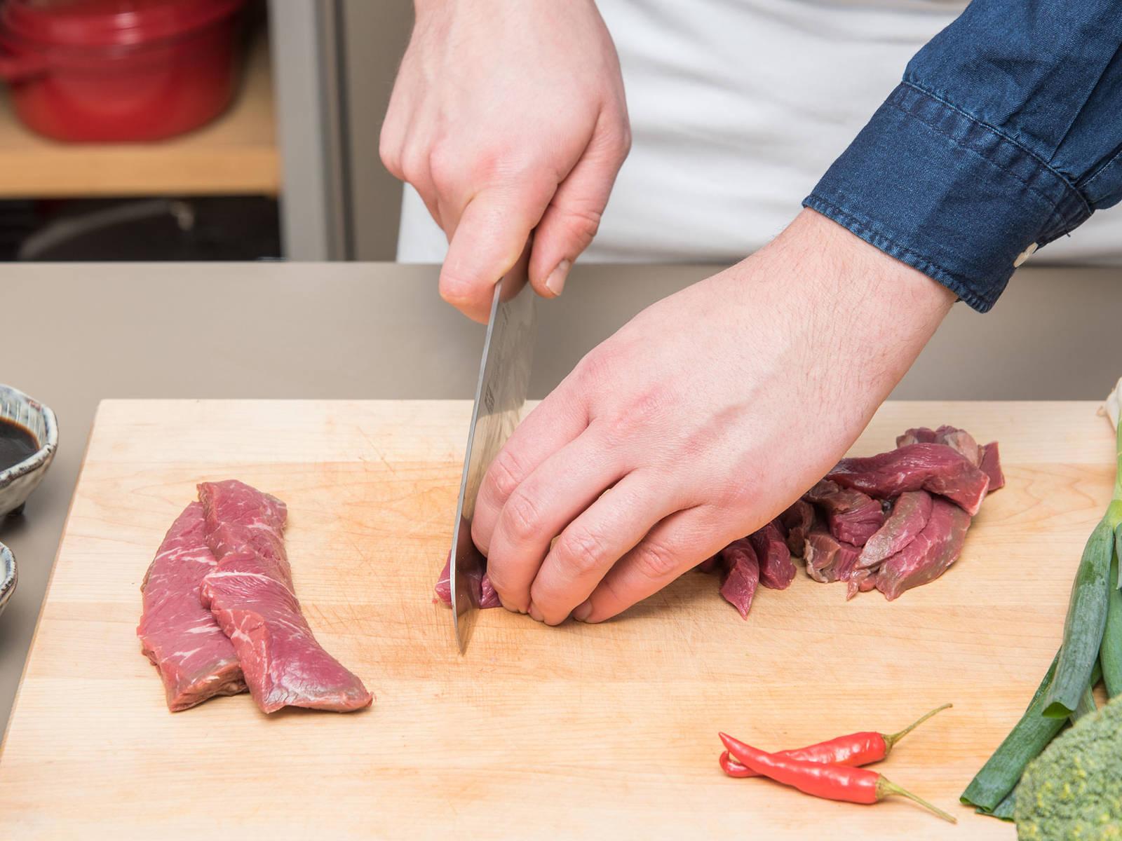 Rinderhüftsteak in dünne Streifen schneiden. Die Hälfte der Sojasauce und des Limettensaftes in eine Schüssel geben. Rindfleischstreifen zugeben, gut vermengen und zum Marinieren beiseitestellen.