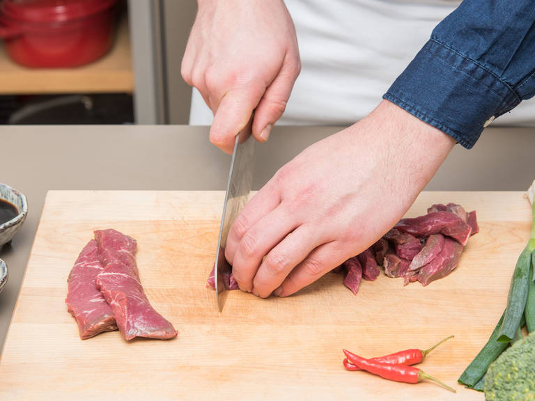 Slice the beef into thin strips. Add half of the soy sauce and juice from half a lime to a bowl. Add beef, tossing to coat, and set aside to marinate.