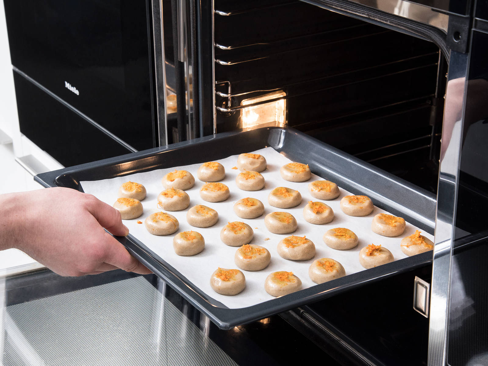 Form the dough into small balls (2 cm/0.8 in). Place them onto a parchment-lined baking sheet and press to flatten them slightly. Sprinkle remaining orange zest on top, and bake at 180°C/350°F for approx. 10 min. Enjoy!