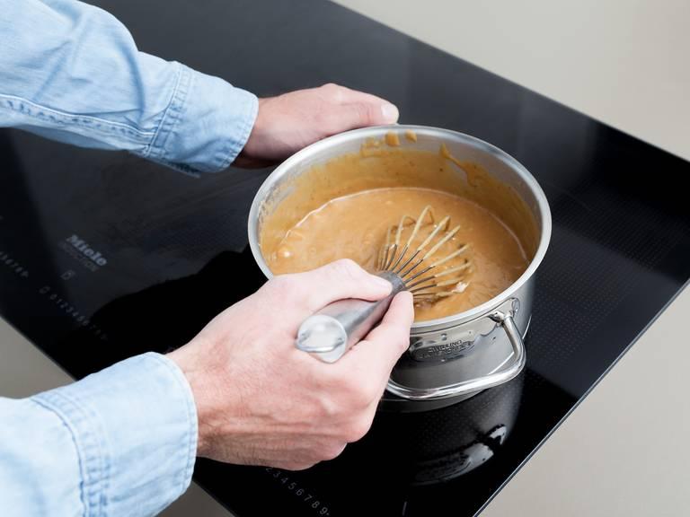 烤面糊期间,将黄油、糖、炼奶和金色糖浆倒入一个大锅中,搅拌混合后煮沸。调小火,煮20分钟,持续搅拌。待混合物颜色变得更深,且质地明显变稠,则关火取下。拌入些许海盐。将焦糖均匀地抹到烤好的脆壳上,然后冷藏至少1小时。