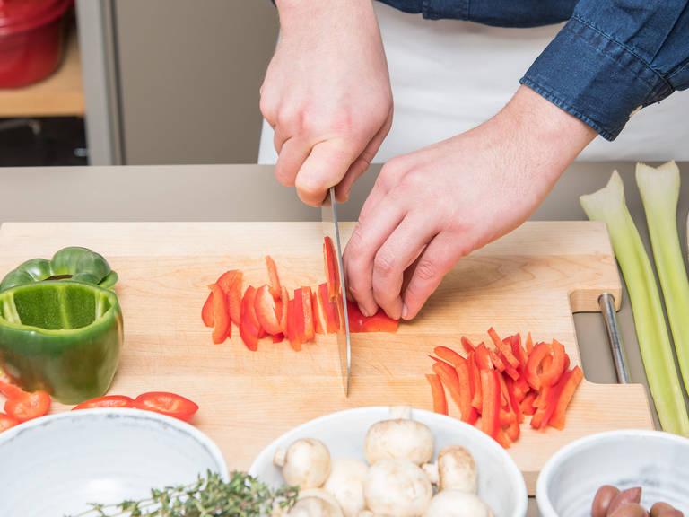 Backofen auf 180°C vorheizen. Zwiebel würfeln und Knoblauch fein hacken. In eine Schüssel geben und beiseitestellen. Rote und grüne Paprika in feine Streifen schneiden, Champignons in feine Scheiben schneiden und Sellerie ebenfalls in feine Streifen schneiden. Das geschnittene Gemüse in eine Schüssel geben. Thymian- und Rosmarinblätter von Zweigen entfernen. Zusammen mit Salbeiblättern fein hacken und beiseitelegen.