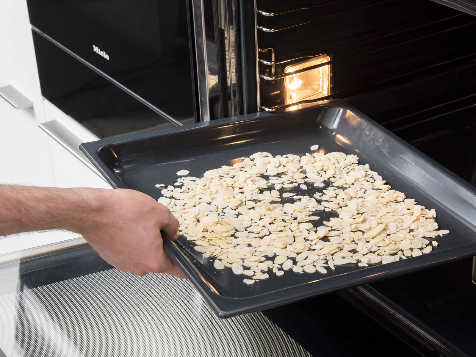 将杏仁片倒入一个烤盘中,放入烤箱烤10分钟或直至杏仁片变成金棕色,取出放凉。