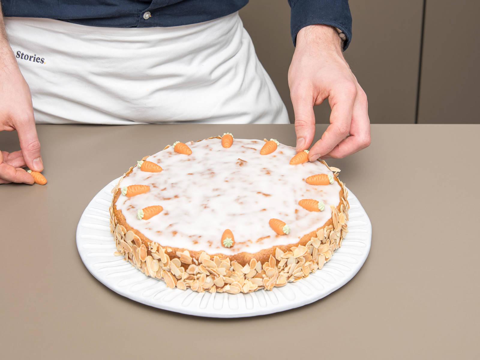 将糖粉过筛倒入小碗中,倒入些许水,制成浓厚糖霜。用扁刮刀将杏子酱抹到蛋糕上,并均匀地刷上糖霜。用烤好的杏仁片装饰蛋糕侧面,在顶上插上小胡萝卜。尽情享用吧!