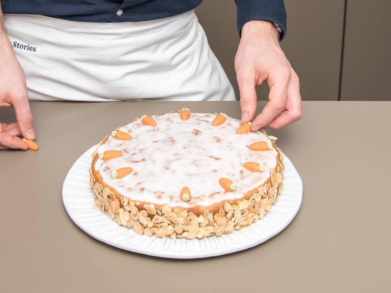 Puderzucker in eine kleine Schüssel sieben. Wasser dazugeben und zu einem dickflüssigen Zuckerguss vermengen. Den abgekühlten Karottenkuchen mit Aprikosenkonfitüre bestreichen und den Zuckerguss gleichmäßig darüber verteilen. Die Seiten des Kuchens mit gerösteten gehobelten Mandeln verzieren. Marzipan-Rübli auf den Zuckerguss legen. Guten Appetit!