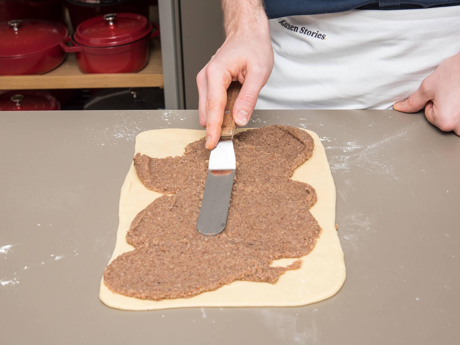 将烤箱预热至160℃。在工作台上撒些面粉。将面团擀成40 x 50厘米的长方形。用抹刀将榛子粉混合物抹到面团上。