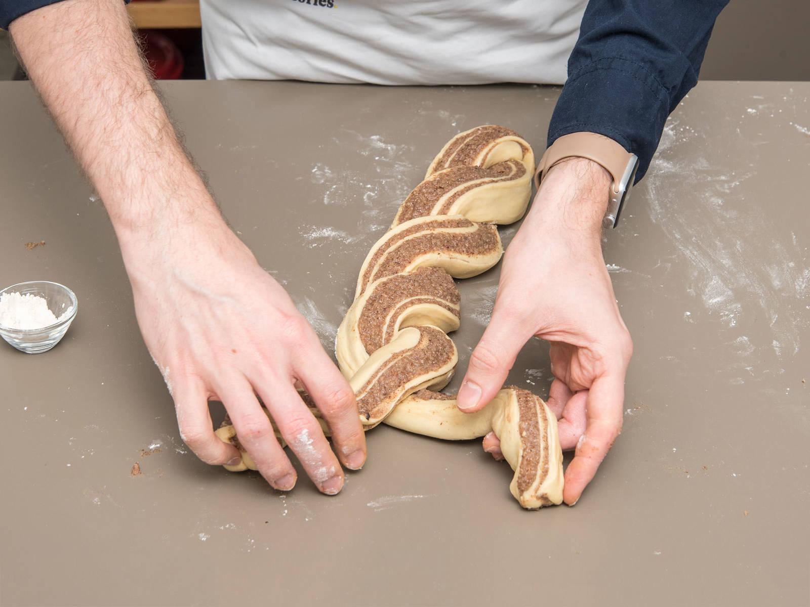从短的一边将面团卷起,纵向将其切半,然后小心地将两条面卷编成辫子。