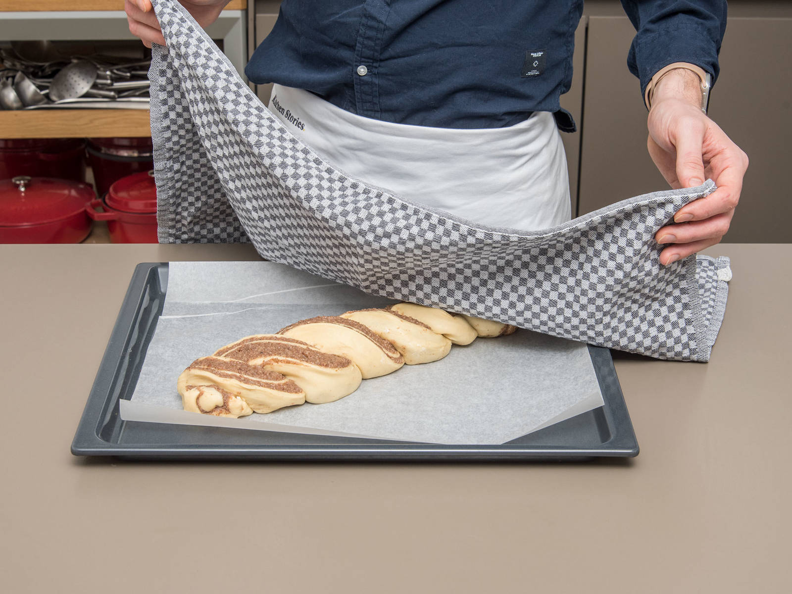 将编好的面包放入铺了烘焙纸的烤盘上。盖上厨房纸,静置30分钟。