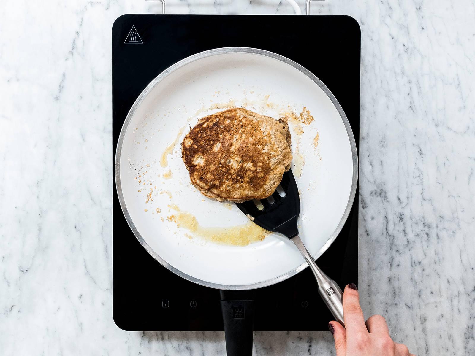 Butter in einer Pfanne über mittlerer Hitze schmelzen. Etwas Teig kreisförmig in die Pfanne geben und mit Schokotröpfchen bestreuen. Solange braten, bis der Teig leichte Blasen schlägt. Anschließend wenden und weiter braten bis der Pancake goldbraun ist. Mit restlichem Teig und Schokotröpfchen wiederholen bis beides aufgebraucht ist.