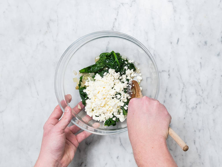 Wash and dry spinach. Peel onions and dice. Heat some oil in a frying pan set over medium-high heat, add spinach and onion and sauté briefly. Season with salt, pepper, and nutmeg to taste. Remove from pan, add to a bowl, and let cool. Crumble feta into the bowl and fold in the spinach.